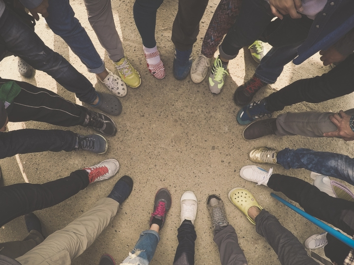 Top view of feet of people standing in a circle. Runners standing in a huddle with their feet together.